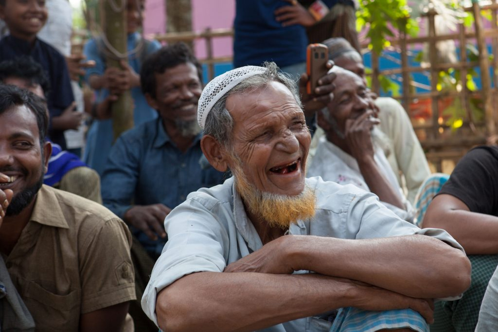 man laughing in a group with a group of people