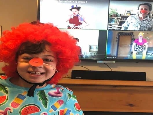 child watching clowns on a zoom meeting
